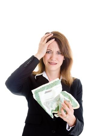 stock certificate: Mujer blanca con expresi�n molesta la celebraci�n de certificado de acciones arrugado. Mano sobre la cabeza. Aisladas sobre fondo blanco. Inversi�n tema fracaso.