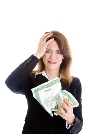 stock certificate: White woman with upset expression holding crumpled stock certificate.  Hand on head. Isolated on white background.  Investment failure theme.