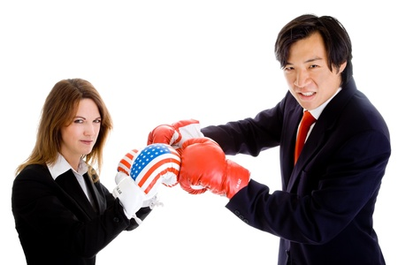 Young white woman in suit and USA flag boxing gloves squared off with Chinese man in suit with red boxing gloves.  U.S. China trade war theme. photo