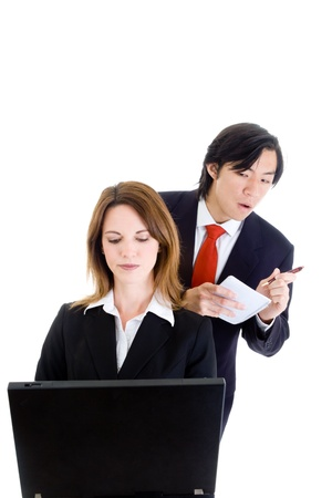Asian man looking over the shoulder of a Caucasian woman working on a computer.  Cheatingindustrial espionage concept.  Isolated on white background. photo