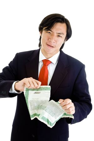 Asian man tearing up stock certificate.  Unhappy about stock marketinvestments.