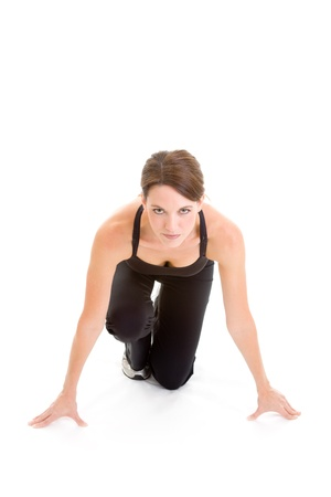 readiness: Woman in starting block position, looking at the camera, ready to sprint.