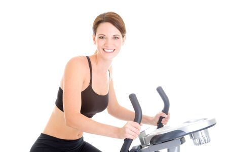 Young Caucasian woman riding an exercise bike.  Isolated on white background. photo