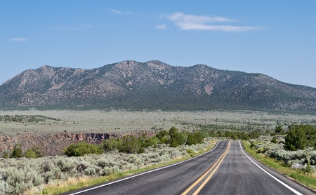 sagebrush: Road running along side the Rio Grande gorge (seen in the center left of picture) outside Taos, NM.  Cerro Chiflo mountain is in background