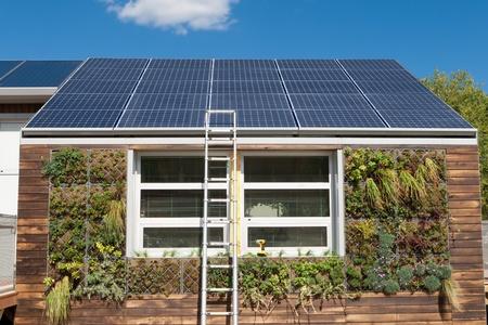 Huis met fotovoltaïsche zonnepanelen en een plant op basis van grijs water terugwin systeem.