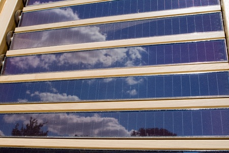 louvered: Louvered solar panels reflecting the sky. Stock Photo