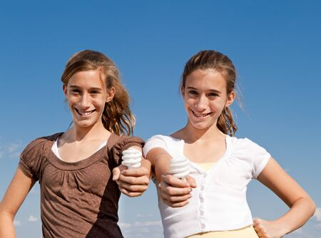 Sisters holding CFL bulbs