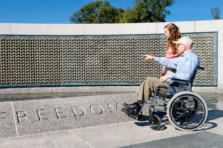 ww2: Older man in a wheelchair and his grand daughter looking at the stars of the fallen at the World War II Memorial in Washington, DC.