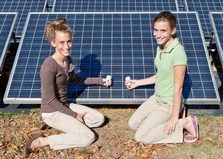 bambine gemelle: Due gemelle tenendo lampade fluorescenti compatte accanto ai pannelli solari