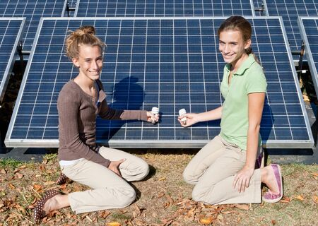 Twin girls holding compact fluorescent bulbs next to solar panels photo