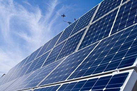 Rows of solar panels with an anemometer on top against bright blue sky