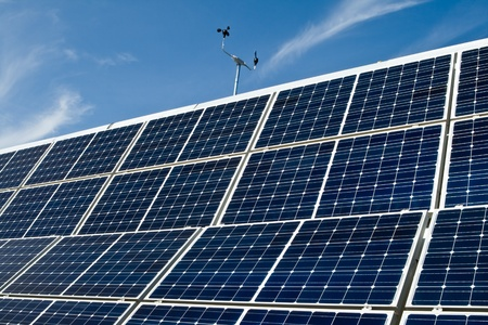 perspective grid: PV solar panel array with an anemometer with a blue sky in the background. Stock Photo