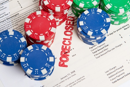 repo: Stacks of poker chips on top of a home foreclosure notice.  Gambling on real estate theme.