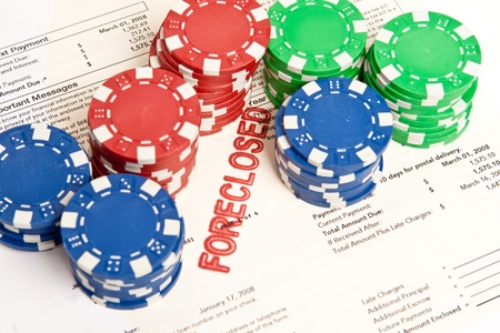 Stacks of poker chips on top of a home foreclosure notice.  Gambling on real estate theme. photo