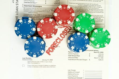 Stacks of poker chips on top of a home foreclosure notice.  Gambling on real estate theme.