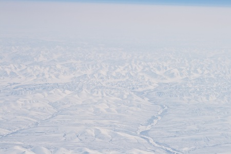 possibly: Snow Covered Verkhoyansk Mountains Aerial Northern Siberia, Russia.  Frozen river possibly the Olenyok River.
