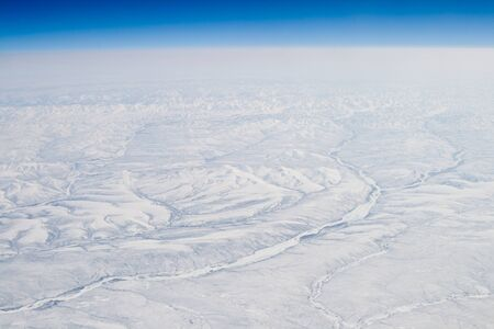 Snow Covered Verkhoyansk Mountains Aerial Northern Siberia, Russia.  Frozen river possibly the Olenyok River