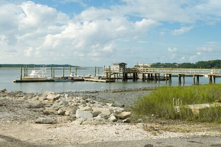 brackish water: Dock on the back bay marsh at low tide.  Hilton Head Island, South Carolina