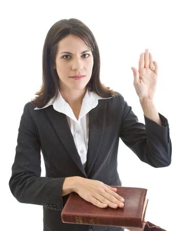 honestidad: Mujer de raza cauc�sica que mira la c�mara y el juramento sobre la Biblia. Aislado en blanco. Foto de archivo
