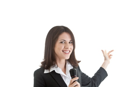 trade show: White woman isolated on white holding a microphone and pointing behind her.  She could be giving a presentation or demonstrating at a trade show booth.  Isolated on white background.