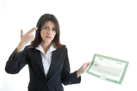 Sad Caucasian woman making gun gesture to her head while holding a stock certificate. Stock Photo - 11397334