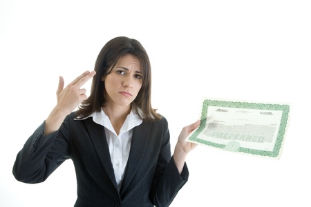 Woman making a gun gesture to her head while holding a stock certificate. photo