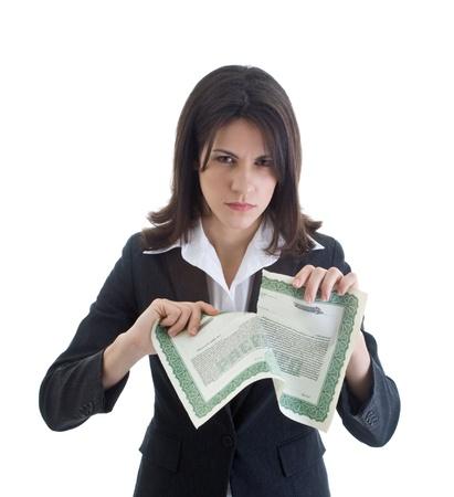 stock certificate: Mujer de raza cauc�sica enojado mirando a la c�mara mientras que rasga un certificado de acciones. Aislado en blanco.