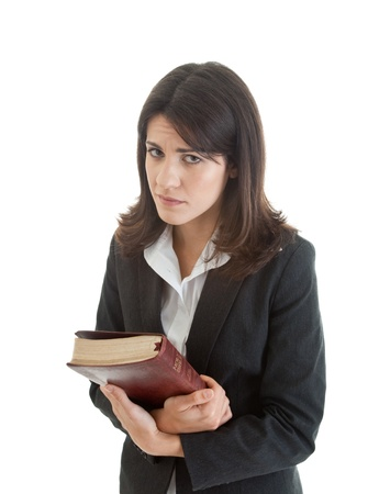 Caucasian woman with mournful expression holding a bible.  Isolated on white background. photo