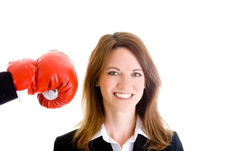 Happy woman unaware she is about to be punched with a boxing glove.  Isolated on white background. photo