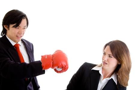 agachado: Hombre asiático puñetazos a una mujer caucásica de traje. Foto de archivo