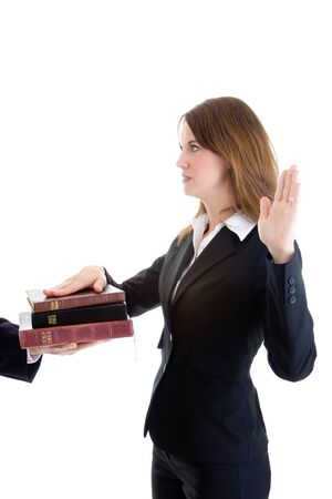 swearing: Side view of young Caucasian woman in a suit swearing on a stack of bibles with arm raised.  Isolated on white background.