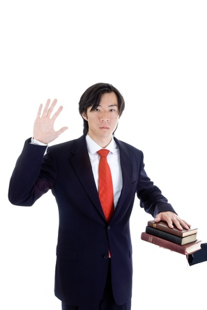 swearing: Asian man in suit swearing on a stack of bibles, with a raised arm.  Isolated on white background.