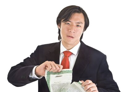 Unhappy Asian man ripping up a stock certificate.  Worthless investment theme.  Isolated White Background. photo
