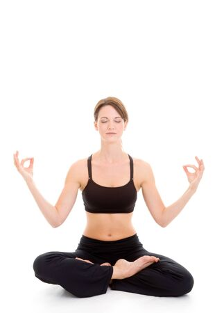 Slender Caucasian woman sitting on the floor in a yoga pose.  Palms press together with legs crossed.  Isolated on white.