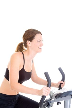 Young Caucasian woman riding an exercise bike photo