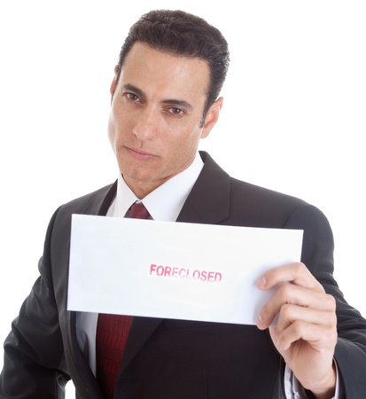 foreclosure: Serious businessman holding an envelope marked Foreclosed.  Isolated on a white background. Stock Photo