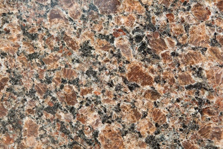 cooled: Large grain reddish granite surface.  Red indicates the presence of iron in the rock, and the large grains means the molten rock cooled very, very slowly giving the rock an opportunity to grow large crystals. Stock Photo