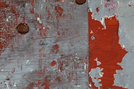 Weathered wood plank with peeling red paint.