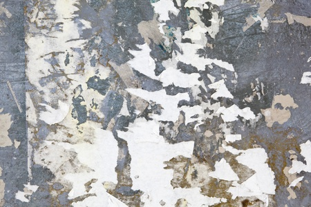 torn metal: Grungy and dirty gray metal surface covered in scraps of paper left by torn posters.