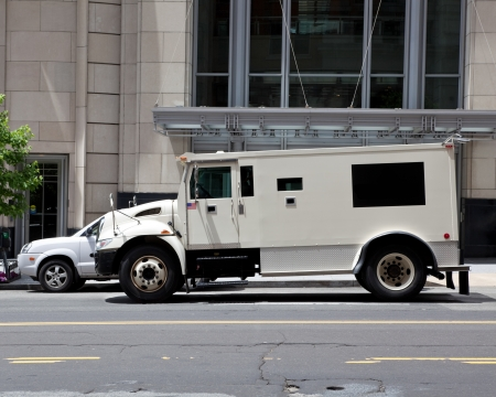 armored: Side view of gray armored double parked on street making a cash pickup.