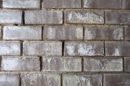 Full frame black brick wall with white mineral stains