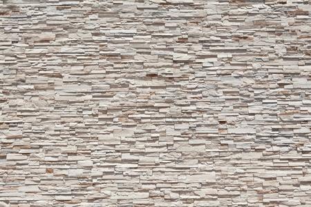 Horizontal full frame sandstone stone wall made from many individual tightly blocks.