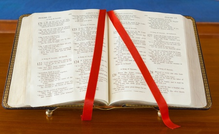 Bible on stand open to the book of Psalms, marked with a red ribbon.