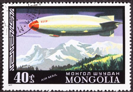 Historic fligth of a Soviet Zeppelin flying over a mountain range canceled Mongolian Air Mail Postage Stamp Stock Photo - 11397145