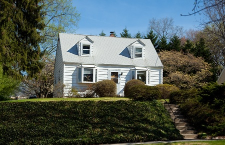 Modest clapboard Cape Cod style single family home in suburban Maryland, USA.  Home is on an ivy covered hill above street
