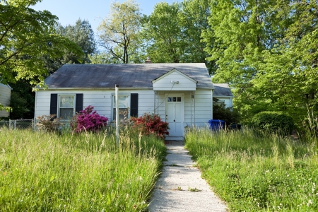 Front vew of unmowed lawn of an abandoned foreclosed Cape Cod style house in suburban Maryland, USA.