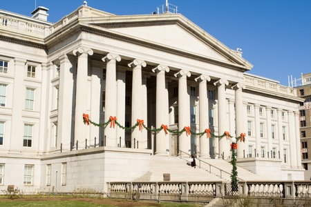federal states: Treasury building in Washington DC decorated for Christmas.  String of pine garlands with red bows attached to the columns of the facade.
