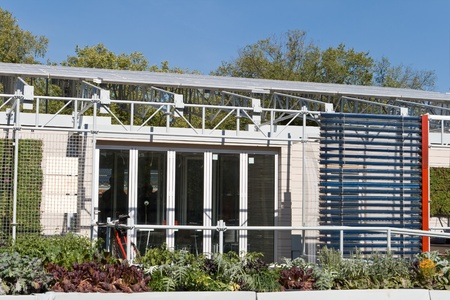 Exterior of a modern solar home with PV panels on the roof and a solar hot water heater on the far right.  Foreground garden is a gray water recovery system.