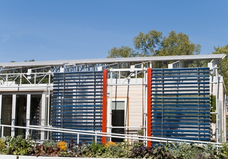 passive: Two racks of solar water heaters on the side of a modern home.  Photovoltaic solar panels on the roof.