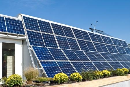 太陽光発電のソーラー パネルと右下隅の屋根の上に太陽熱温水の行を持つ外装のモダンな太陽の家。風速計と同様の屋根に。